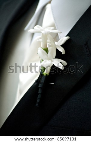 Close-up of a groom with flowers on his lapel