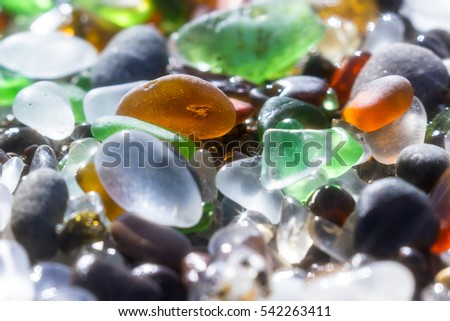 close up of a group of shiny pieces of sea glass on the beach using a star filter to obtain a sparkling effect