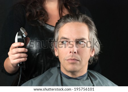 Close-up of a hair stylist preparing to use clipper having removed bulk length. - stock photo