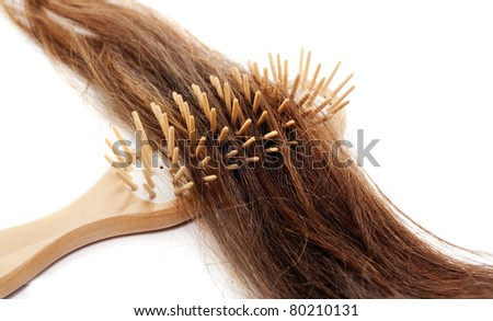 Close-up of a hairbrush with lost hair in it isolated on white - stock photo