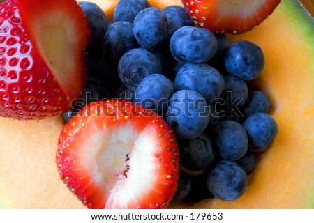 Close up of a half cutted cantaloup, filled with blueberries and strawberries - stock photo