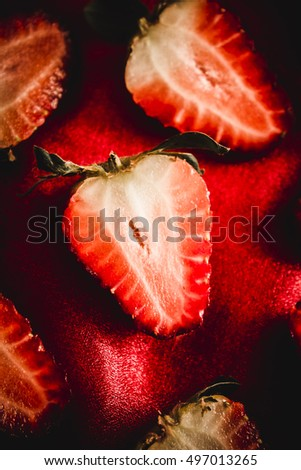 Close up of a half of red ripe strawberry lying on red cloth