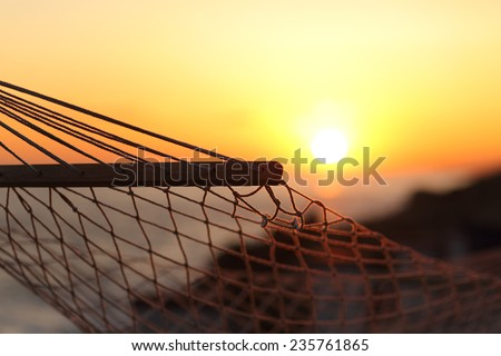 Close up of a hammock on the beach at sunset with the sun in the background - stock photo