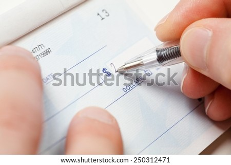 Close up of a hand and pen writing amount on a blank check