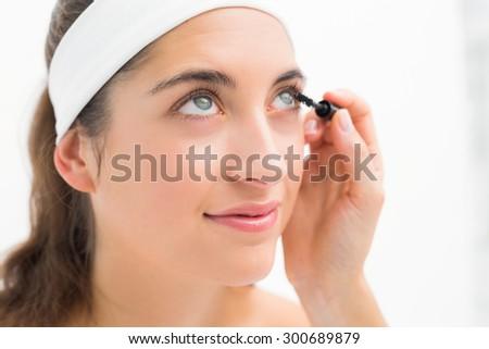 Close up of a hand applying mascara to beautiful woman - stock photo