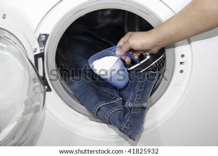Close-up of a hand holding a filled cup of washing powder in front of a washing machine - stock photo