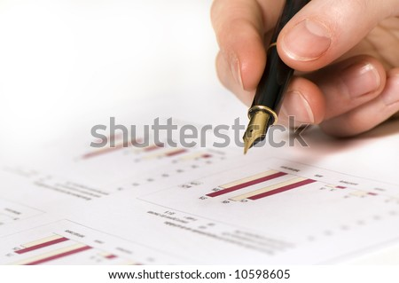 close up of a hand holding a pen above some papers with graphics.