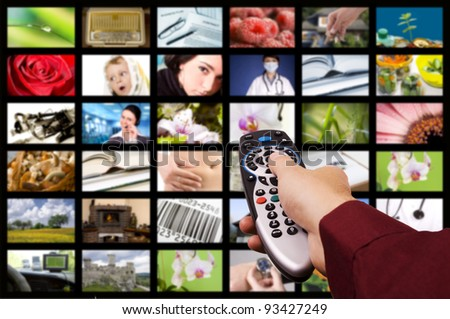 Close up of a hand holding a remote control with a television concept. - stock photo
