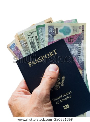 close up of a hand holding an american passport with money form different countries inside of it