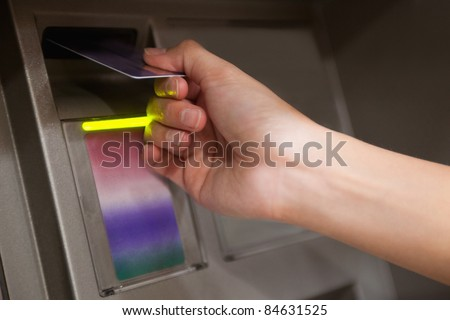 Close up of a hand inserting a credit card in an ATM - stock photo