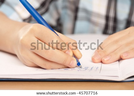 Close up of a hand of a pupil writing homework or examination