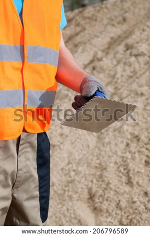 Close-up of a hand of manual worker with grout float - stock photo