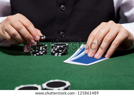Close-up of a hand of poker player with cards and chips