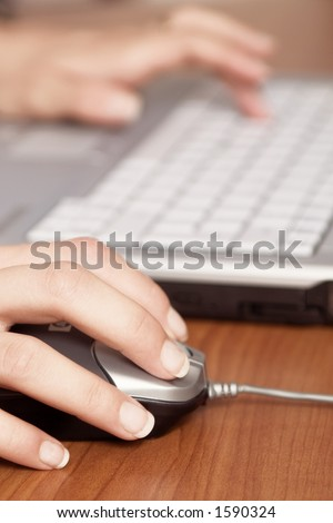 Close-up of a hand on mouse and laptop keyboard in background, blured. - stock photo