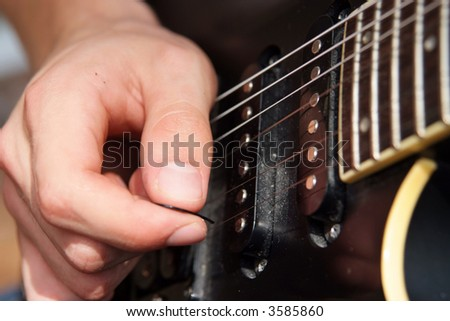 Close up of a hand playing with a pick on an electric guitar - stock photo