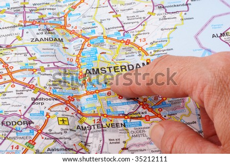Close up of a hand pointing out Amsterdam on the map. - stock photo