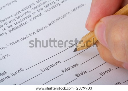 Close up of a hand signing a document. Please note that the signature is fictitious