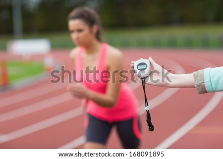 Close-up of a hand timing a blurred young woman's run on the running track - stock photo