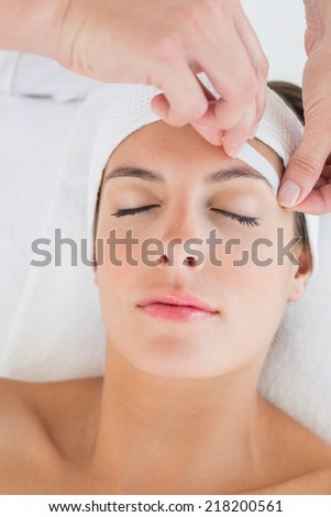 Close up of a hand waxing beautiful womans eyebrow - stock photo