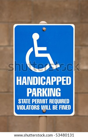 Close up of a handicapped parking sign posted in a parking lot. - stock photo