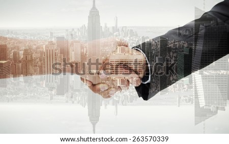 Close up of a handshake against room with large window looking on city - stock photo