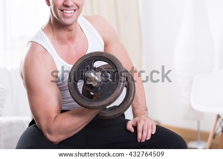 Close up of a handsome man doing strength training at home, holding dumbbell
