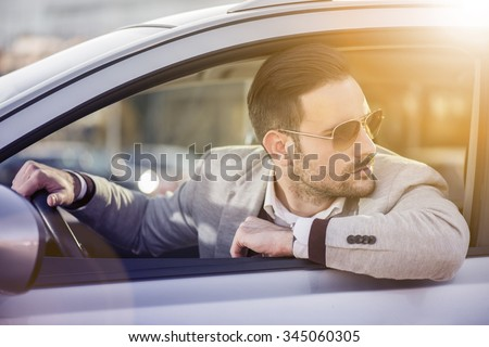 Close up of a handsome man siting in his car.He is wearing a white shirt and a grey suit.