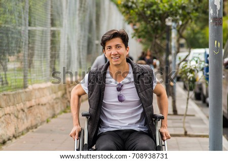Close up of a handsome smiling young disabled man in wheelchair, with both hands in the whees, in the street, in Quito city