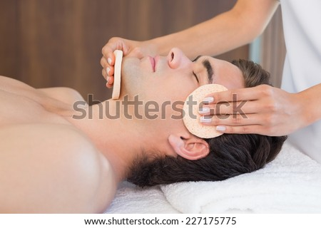 Close -up of a handsome young man receiving facial massage at spa center - stock photo