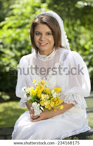 Close-up of a happy, beautiful young bride among summer foliage. - stock photo