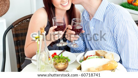Close-up of a happy boyfriend kissing his beautiful girlfriend during dinner at home - stock photo
