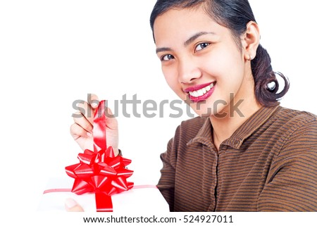 Close up of a happy lady opening a gift. Isolated in white background.