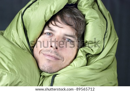 Close-up of a happy man wrapped up in a down mummy sleeping bag. - stock photo