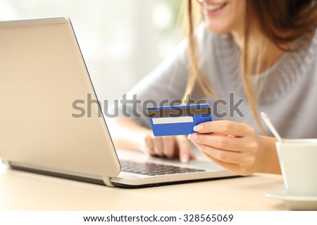 Close up of a happy woman hand buying online with a laptop and paying with a credit card - stock photo