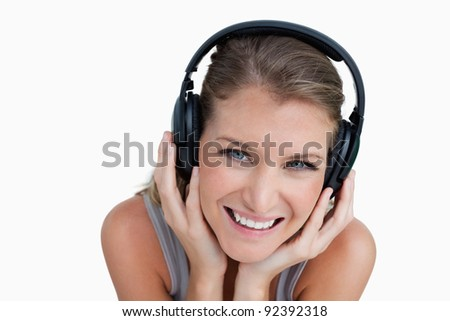 Close up of a happy woman listening to music against a white background