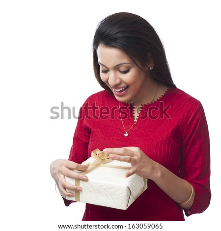 Close-up of a happy woman opening a gift box - stock photo