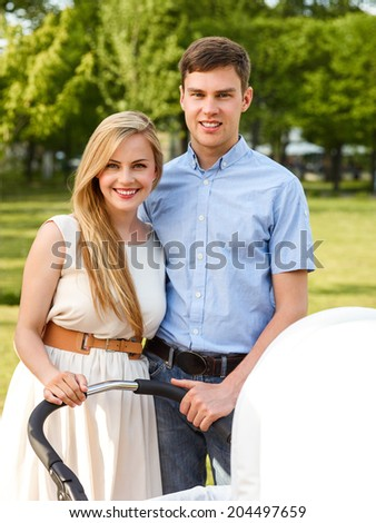 Close-up Of A Happy Young Couple In Park With Baby Carriage - stock photo