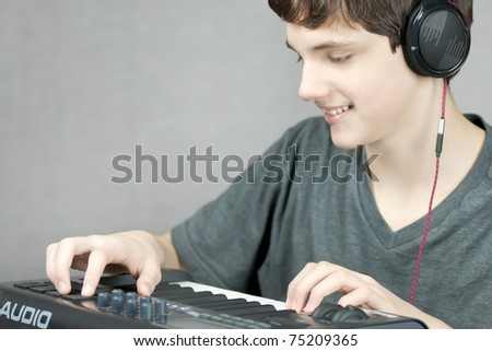 Close-up of a headphone wearing teen adjusting his keyboard. - stock photo