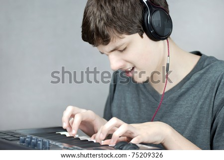Close-up of a headphone wearing teen playing his keyboard. - stock photo