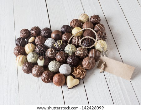 Close-up of a heart shape made with various types of chocolate truffles and a blank tag for copy-space over a white wooden table - stock photo