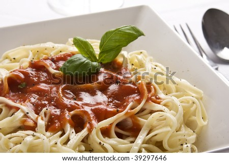 Close up of a homemade plate of pasta with tomato sauce and basil. - stock photo