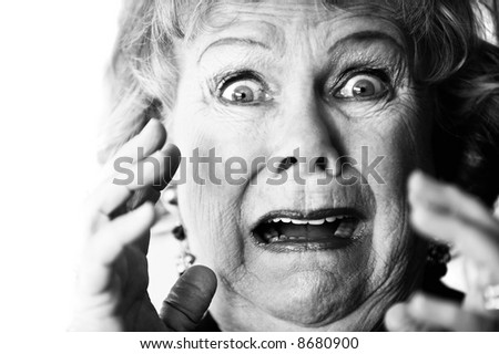 Close-up of a horrified senior woman with her mouth open. - stock photo