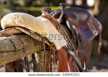 Close-up of a horse saddle on top of a wooden fence of the paddock - stock photo