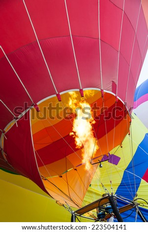 Close up of a hot air balloon flame inflating a red balloon with other balloons in the background. - stock photo