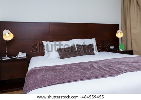 close up of a hotel room bedroom with a king size bed in a modern setting
