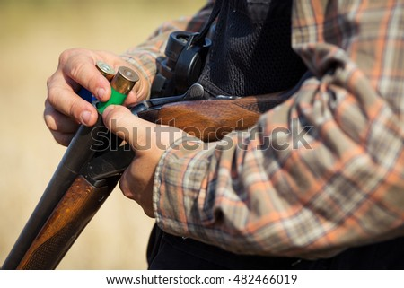 Close-up of a hunter loading his shotgun