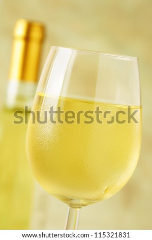 Close-up of a ice cold glass of white wine covered with water drops - condensation - stock photo