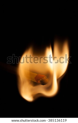 Close-up of a igniting matchstick, isolated on black background. - stock photo