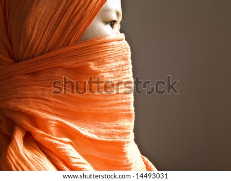 Close-up of a islamic woman covered with a orange veil