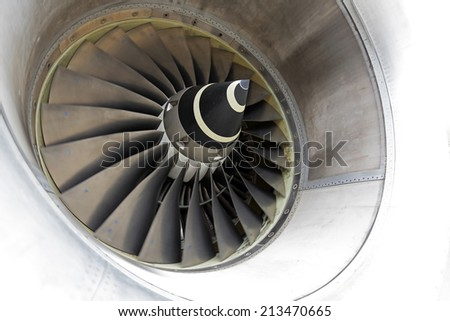 Close-up of a jet engine with slowly moving blades. - stock photo